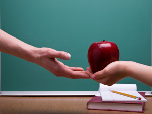 Student giving teacher and apple.